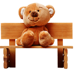 little teddy bear seating on the bench
